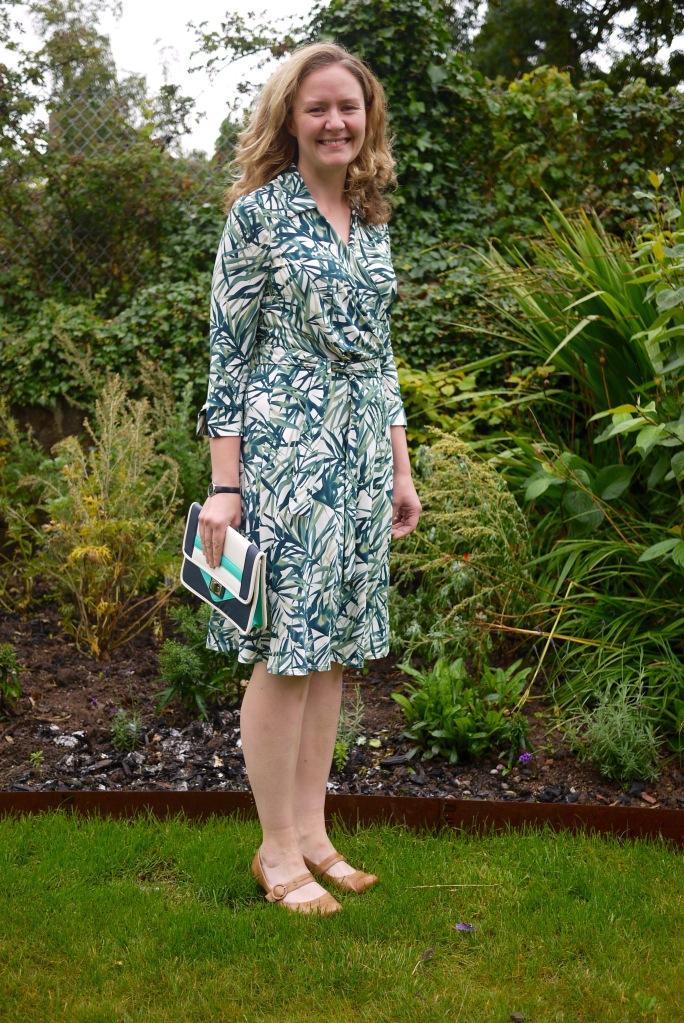 Woman wearing leaf-print wrap dress standing in garden