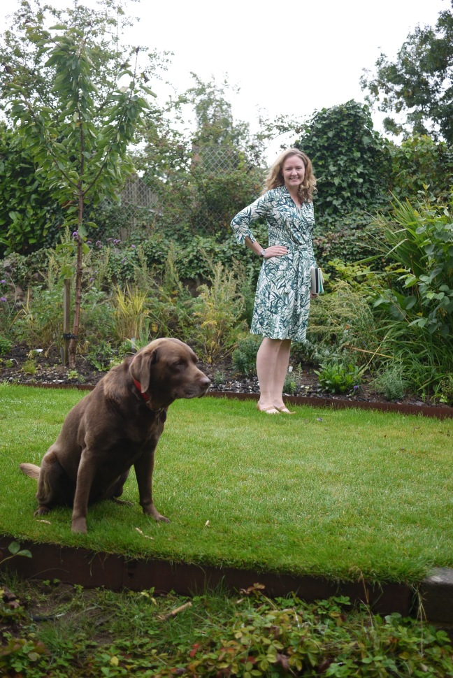 Woman standing in garden wearing leaf-print wrap dress. Chocolate Labrador in foreground.