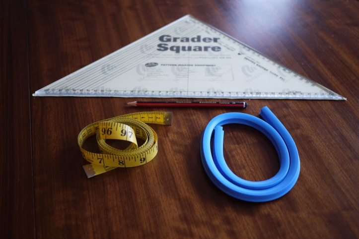 Pattern grading square, tape measure, french curve and pencil