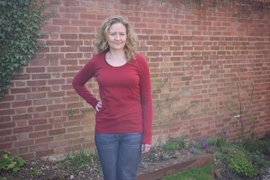 Janet wearing a red scoop neck jersey T-shirt standing in front of a wall.