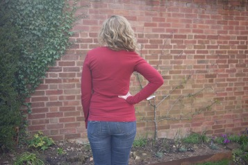 Rear view of Janet wearing a red T-shirt. The fabric is pooling at the back waist.