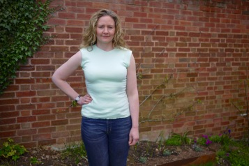 Janet wearing another mint green T-shirt, standing in front of a wall.