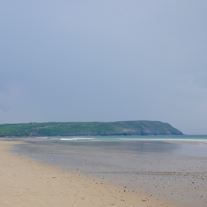 Image of an empty sandy beach with a headland in the background.