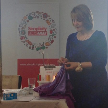 May Martin holding a length of purple jersey fabric.