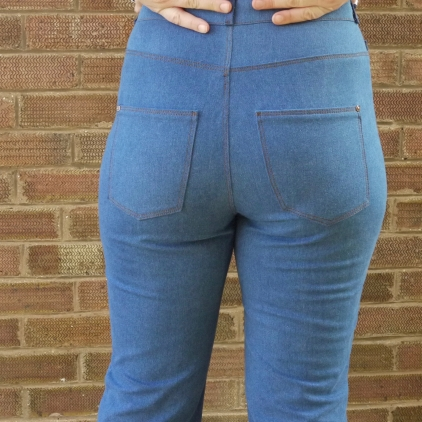 Back view of blue jeans with brown topstitching on the pockets