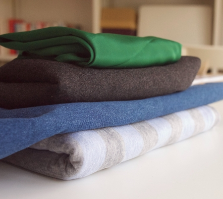 Stack of four folded fabrics: two polyester, two cotton
