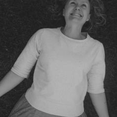 woman lying down wearing cream-coloured 3/4 length sleeve sweatshirt