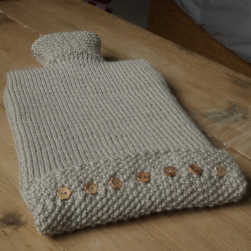 Beige knitted hot water bottle cover with wooden buttons