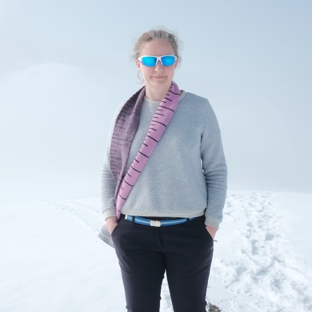 Woman wearing grey sweatshirt, a pink scarf and blue wrap-around sunglasses standing in a snowy landscape